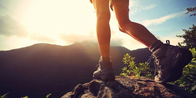 A hiker walking into beautiful sun