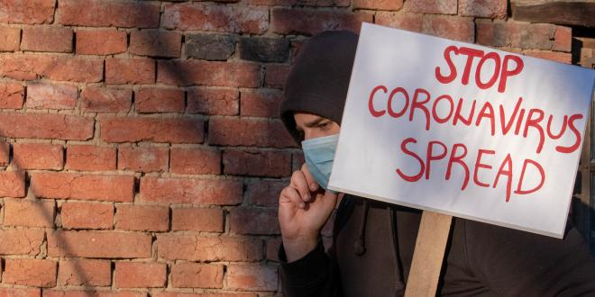 A man in a face mask carrying a sign that reads stop coronavirus spread.
